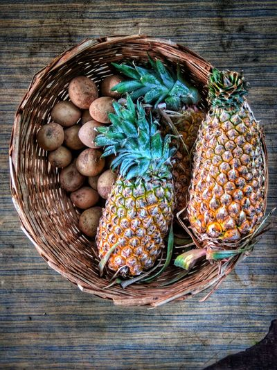 Pineapples and Chikus in a baskst Fruits ♡ Sapota Fruits Pineapple Farmfresh Food Organic Basket Table Directly Above High Angle View Close-up