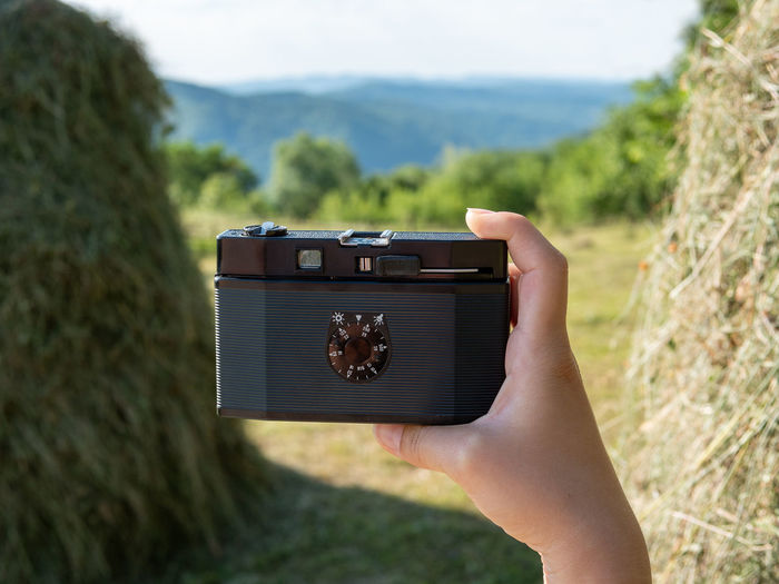 Midsection of person photographing camera on land