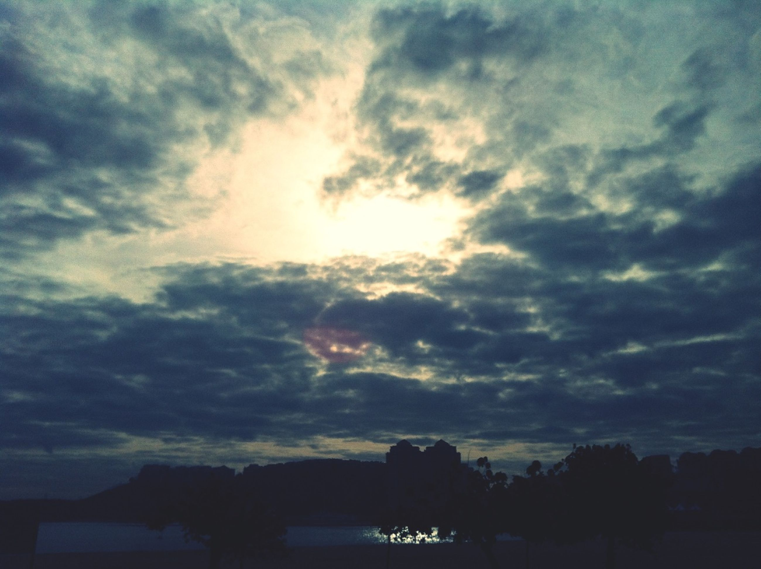 silhouette, sky, cloud - sky, tranquil scene, scenics, beauty in nature, tranquility, sunset, cloudy, nature, cloud, idyllic, sun, tree, sunbeam, weather, sunlight, dramatic sky, outdoors, cloudscape