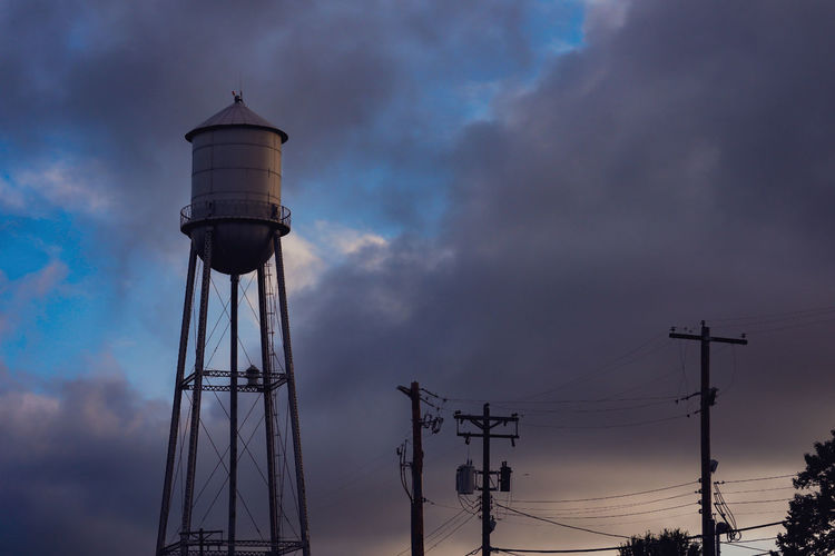 Low angle view of water tower against sky at sunset
