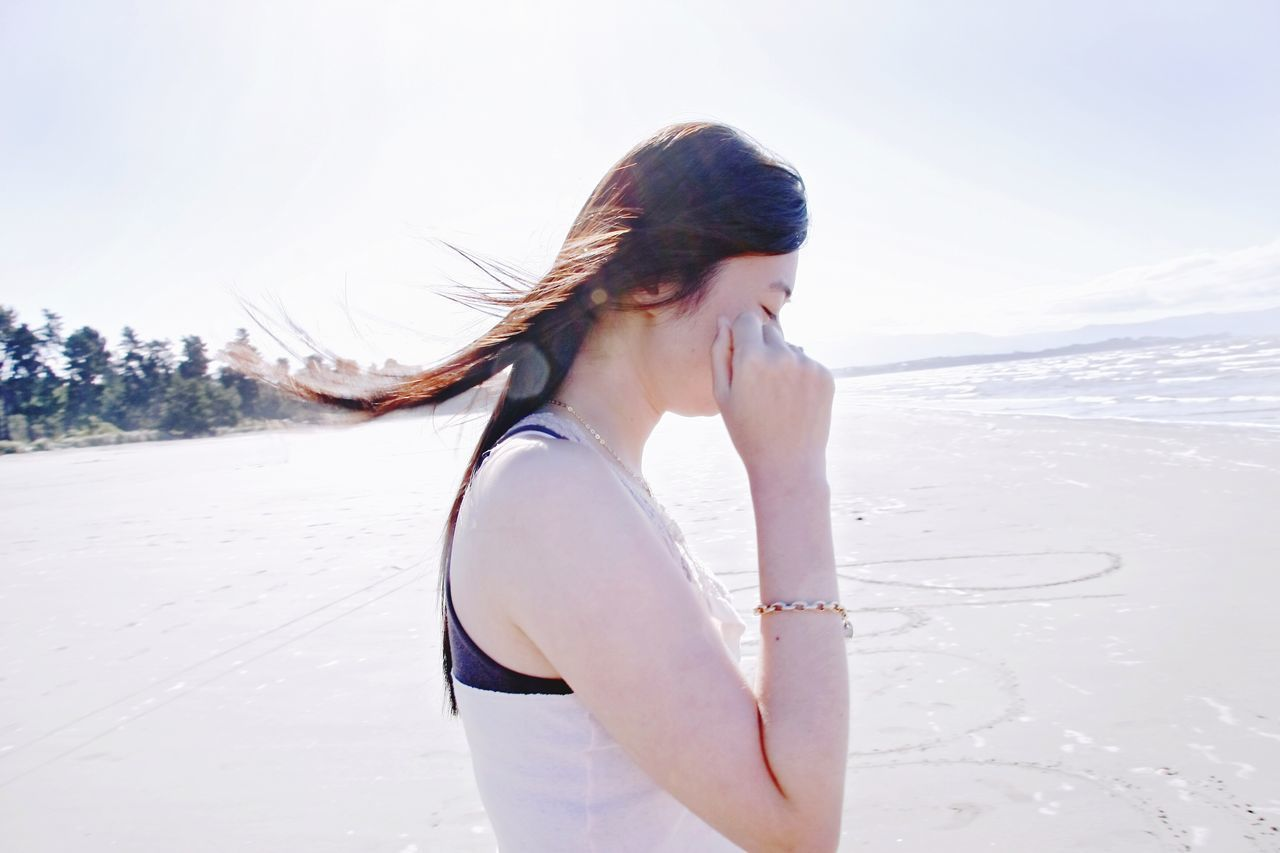 Side View Of Young Woman Touching Cheeks On Beach