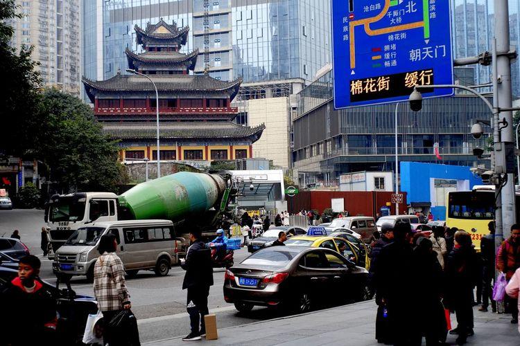 People on city street against buildings