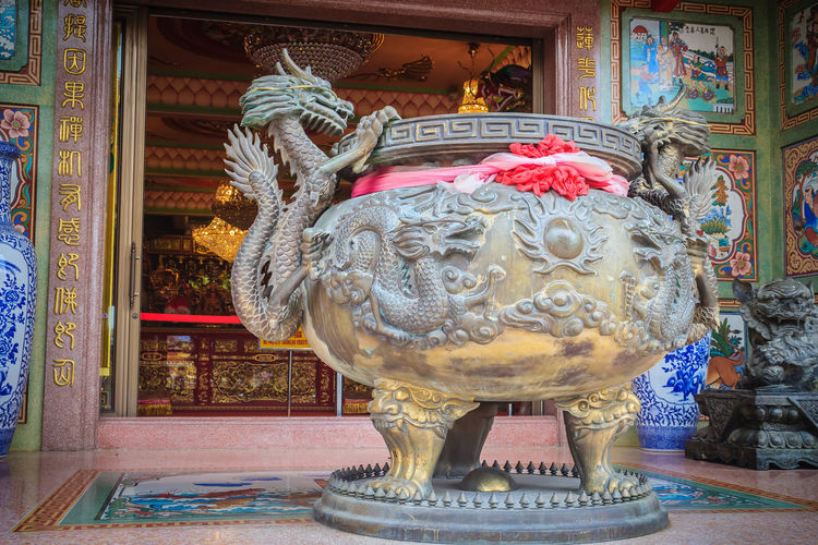 Beautiful dragon sculpture on incense pot burner in the public Chinese temple. Dragon Incense Burn To Worship The Buddha And The Sacred. Incense Burner To Worship Holy Things And Buddha. Architecture Art And Craft Belief Building Built Structure Craft Creativity Dragon Pot Human Representation Incense Burner Incense Burner. Incense Burners Incense Pot Incense Smoke Incense Stick Incense Sticks Indoors  Male Likeness No People Ornate Pattern Place Of Worship Religion Representation Sculpture Spirituality Statue