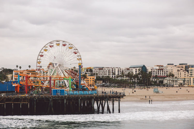 Santa Monica Pier At Beach By Amusement Park Against Cloudy Sky