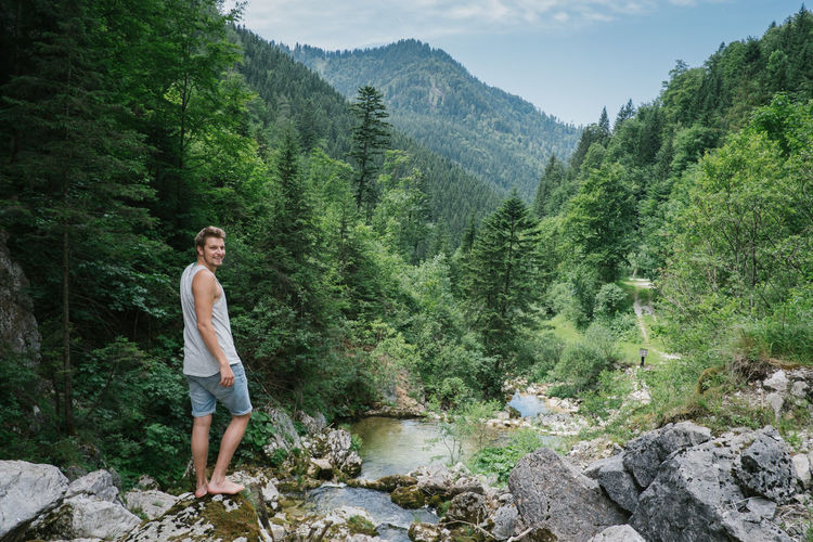 Portrait of smiling young man standing on rock by stream in forest