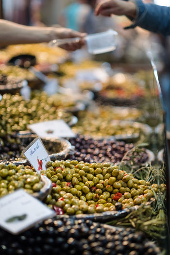 mixed olives on display in market with vendor filling a box in the background Box EyeEmNewHere Close-up Customer  Day Display Food Food And Drink For Sale Freshness Healthy Eating Large Group Of Objects Market Market Stall Olives Price Tag Real People Retail  Selective Focus Shop Display Store Vendor