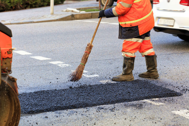 People working on road in city