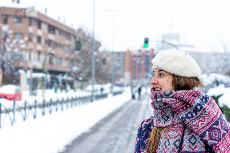 Woman looking away in snow during winter