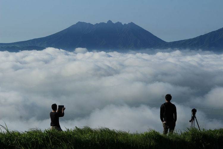 Two people overlooking clouds against mountains