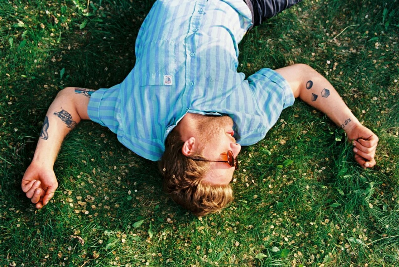 MAN RELAXING ON GRASSY FIELD