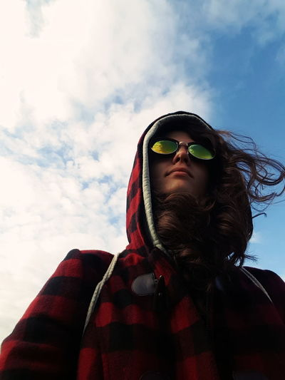 Low Angle View Of Young Woman In Sunglasses Against Sky