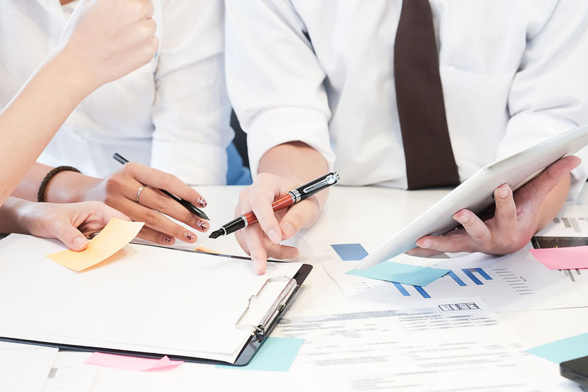 Business people Consulting and business planning. Adult Clothing Coworker Expertise Hand Holding Human Body Part Human Hand Indoors  Men Midsection Occupation Office Paper Pen People Professional Occupation Real People Table Working Writing