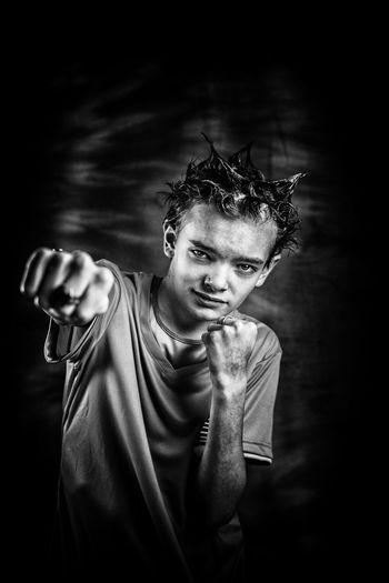 Portrait of teenage boy punching against black background