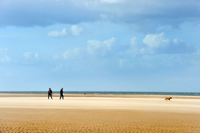 Walking the Dog on the beach near Burnham Overy Staithe, Norfolk Norfolk Beach Cloud - Sky Day Dog England Horizon Horizon Over Water Leisure Activity Real People Sand Sea Sky Togetherness Walking Water Windswept Windy