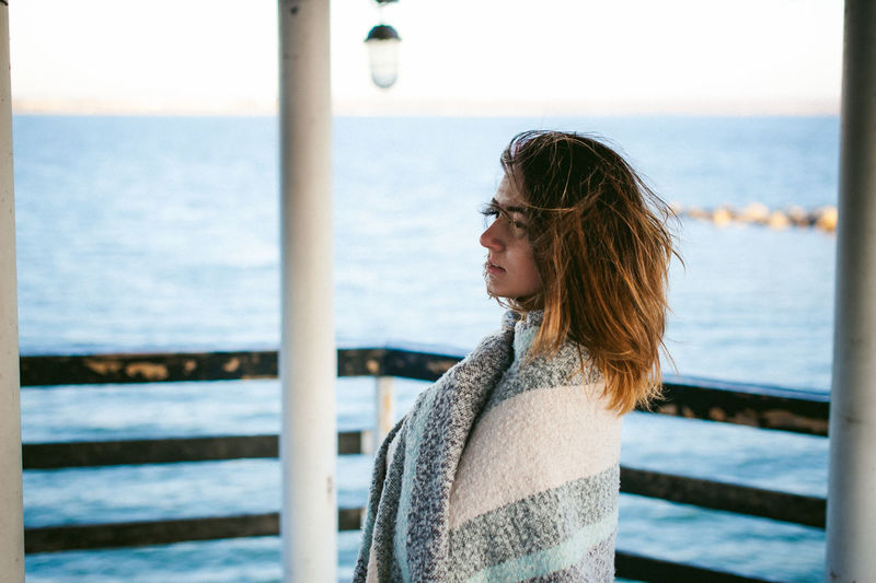 Thoughtful young woman standing on pier over sea
