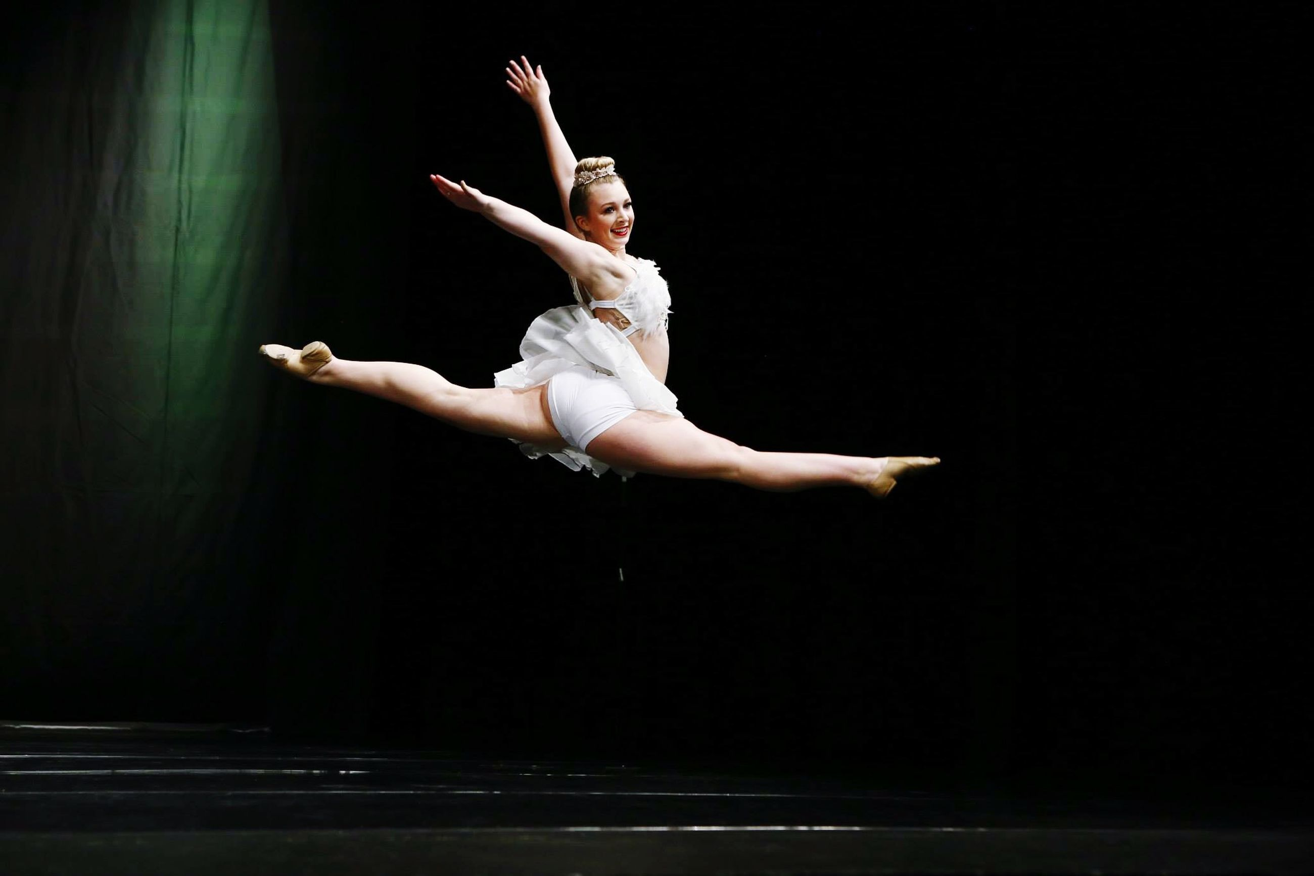 night, full length, mid-air, lifestyles, jumping, leisure activity, copy space, side view, person, skill, arms raised, indoors, motion, arms outstretched, performance, holding, vitality