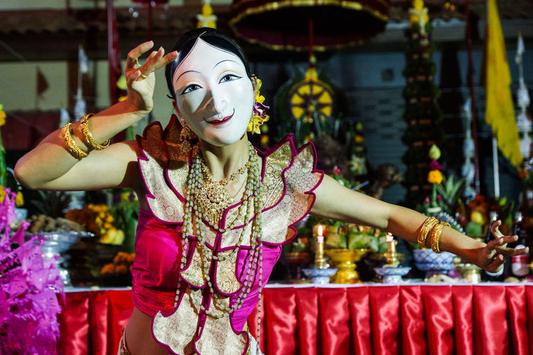 Woman in mask dancing during traditional festival