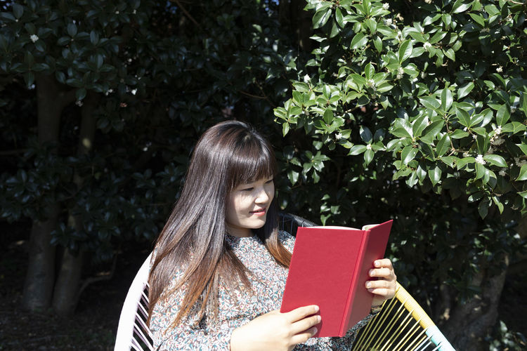 Young woman reading book against tree
