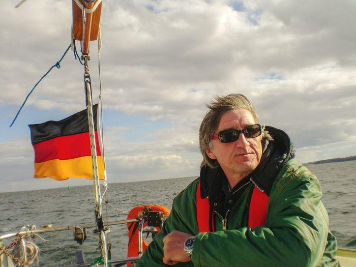 Man wearing sunglasses in boat on sea against sky