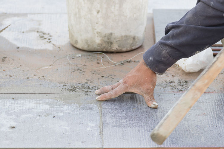 Cropped hand of man laying tiles on floor