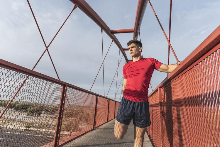 Athlete stretching on footbridge against sky