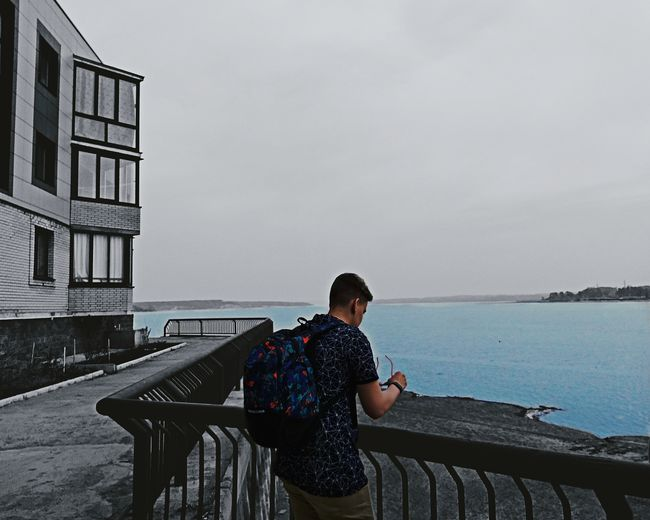 Side view of man with backpack standing by railing against sea