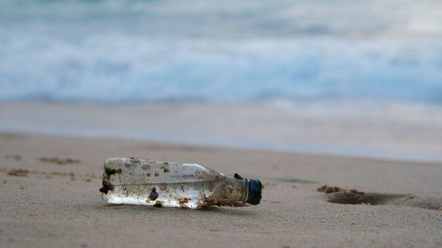 Close-up of abandoned bottle on beach