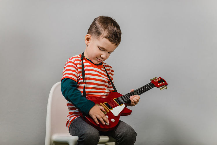 Child playing electric guitar. Portrait of young boy playing children acoustic guitar against grey background - studio shot. Child Portrait Playing Play Guitar Isolated Grey Gray Background One Person Music Sitting Musical Equipment Boy Caucasian Studio Studio Shot Electric Guitar Musician Talent Talented 3-5 Years Stripes T-shirt Red Color