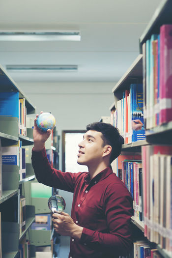 Young man holding globe amidst bookshelves in library