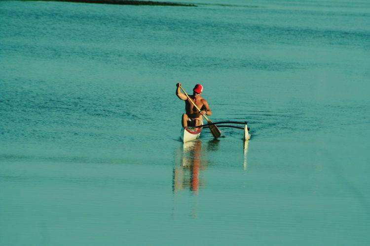 Shirtless Man Canoeing In Water