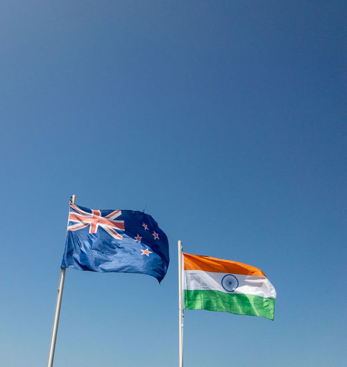 The new zealand and indian flags flutter in the wind under a clear blue sky