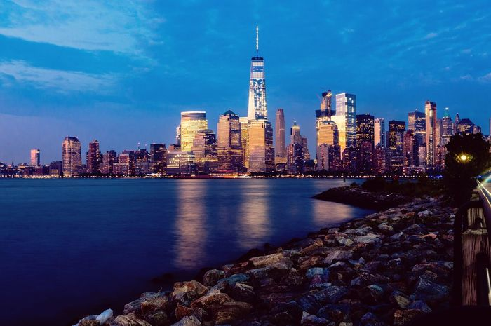 The sun sets over the Manhattan skyline, illuminating the buildings with a fiery hue as the city lights turn on for the night. Showcase June Liberty State Park Newyorkcity Newjersey Manhattan Enjoying Life Taking Photos City Life Citylights Timelapsephotography Frame Relaxing Water CoolNight