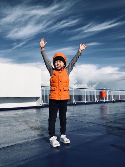 Full length of cute boy standing with arms raised on pier