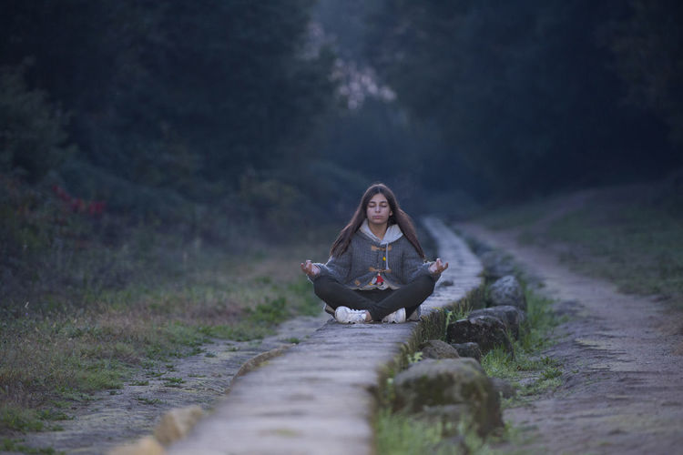 Young Woman Doing Yoga On Pathway