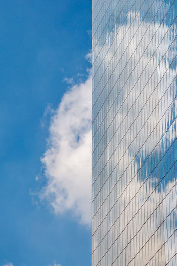 Low angle view of modern building with clouds reflection against sky