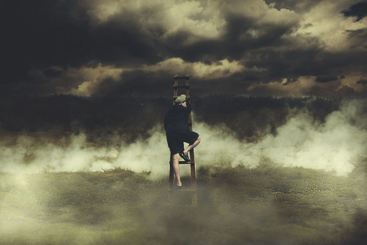 Rear View Of Man Climbing On Ladder At Foggy Field Against Cloudy Sky