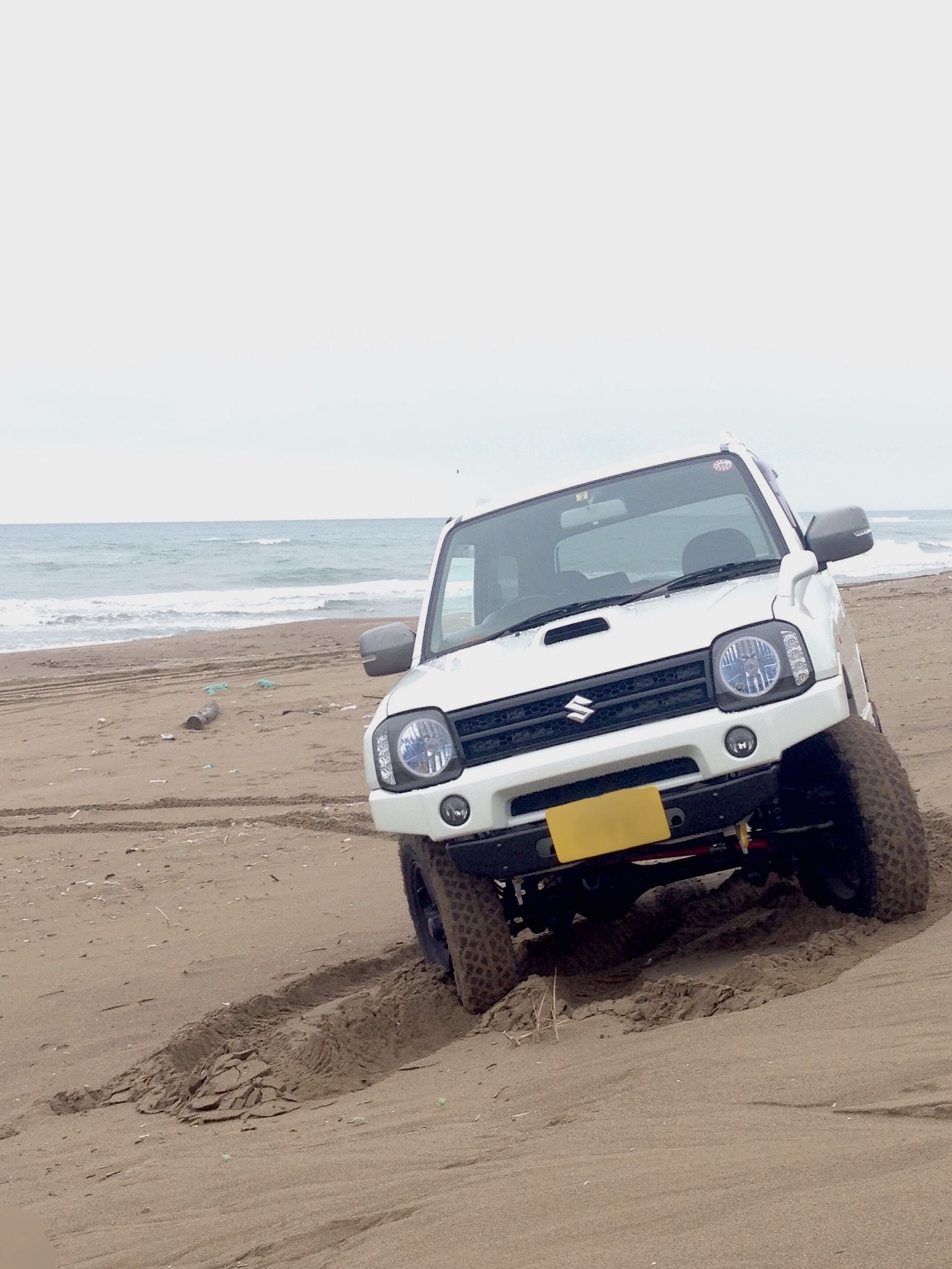 beach, sand, land vehicle, sea, transportation, mode of transport, horizon over water, shore, car, clear sky, day, stationary, sunlight, outdoors, sky, travel, copy space, nature, water, no people