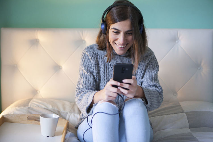 Smiling woman using smart phone while sitting on sofa
