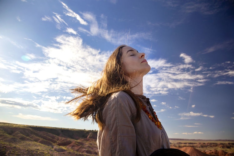 Woman looking away while standing on land against sky