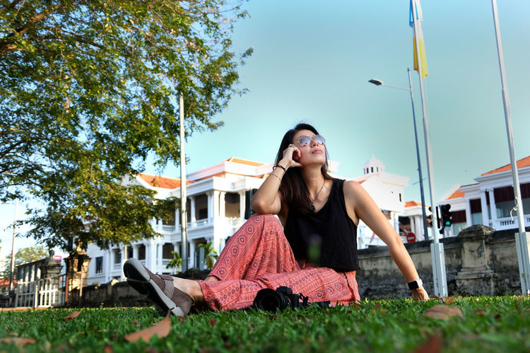 Women sitting on the ground Architecture Built Structure Building Exterior Young Women Sky Nature Leisure Activity Lifestyles Emotion Real People Front View Happiness One Person Smiling Tree Casual Clothing Beautiful Woman Hairstyle Women