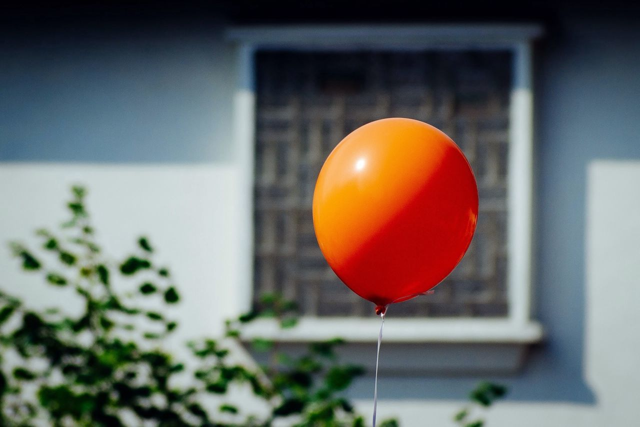 Close-up of a orange balloon against window