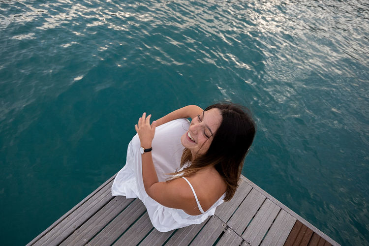 High angle view of woman sitting on wood by sea