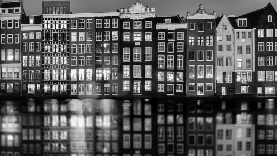 Buildings reflecting on canal at night