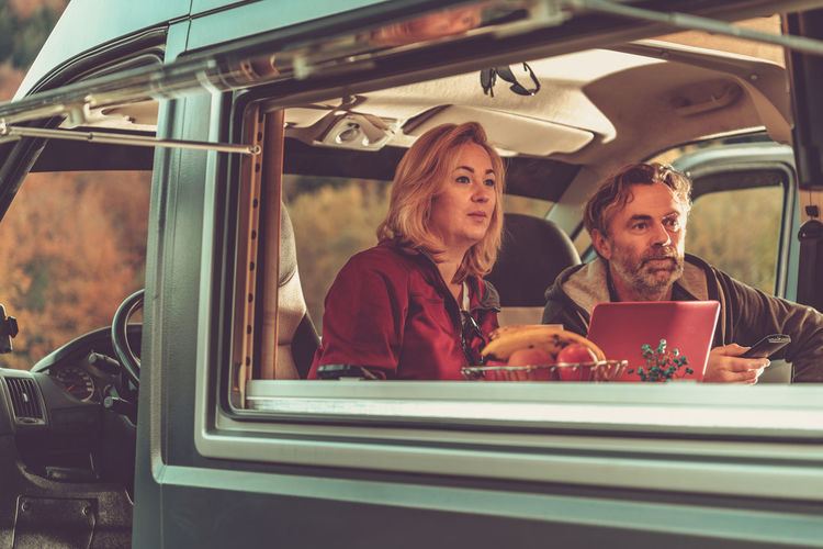 Couple watching tv while sitting at motor home