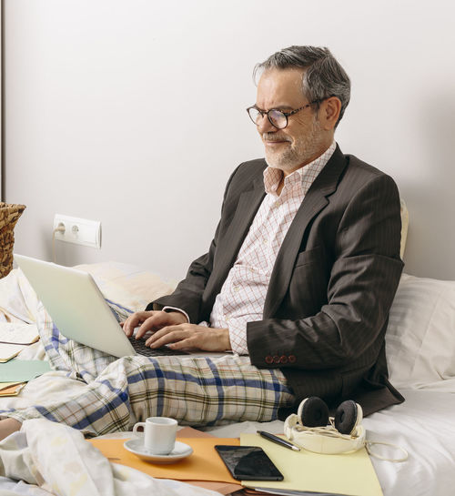 Man using mobile phone while sitting on bed