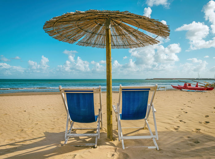 Scenic view of beach chairs on sandy beach