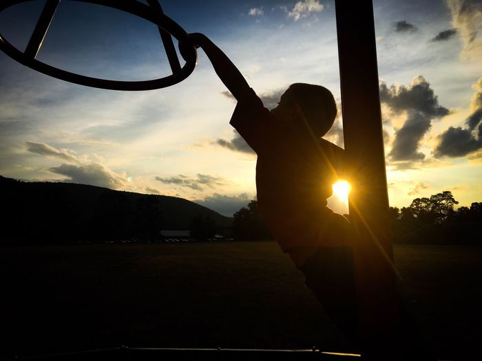 Sunset playtime Silhouette Real People Sunlight Sunset Sky Lifestyles One Person Leisure Activity Sunbeam Sun Outdoors Day