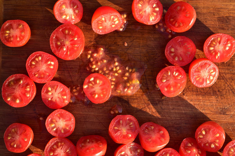 Above view of grape tomatoes cut into halves on wood cutting board