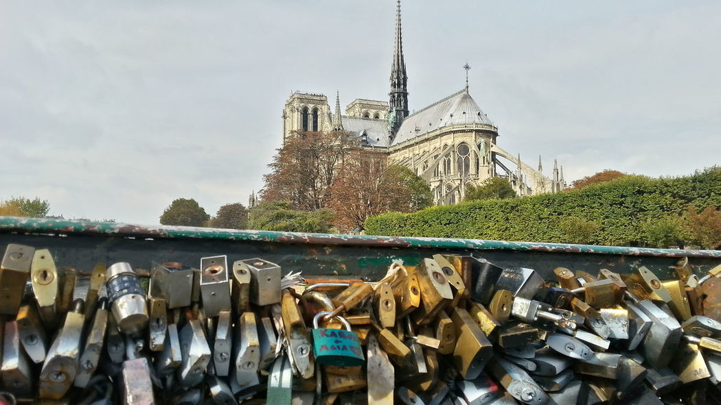 Architecture Bridge - Man Made Structure Building Exterior Built Structure Day Hanging Lock Love Lock No People Notre Dame De Paris Outdoors Padlock Paris Place Of Worship Railing Religion Sky Spirituality