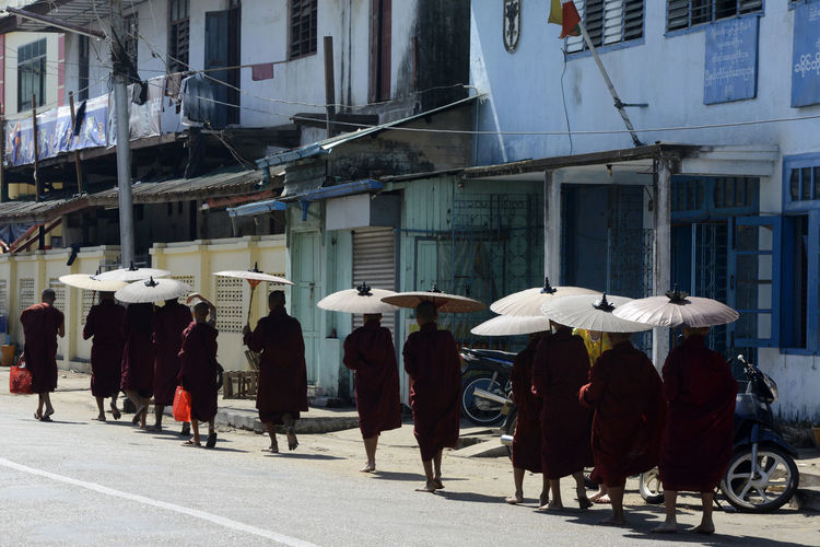 Monks Walking On Road By Buildings During Sunny Day